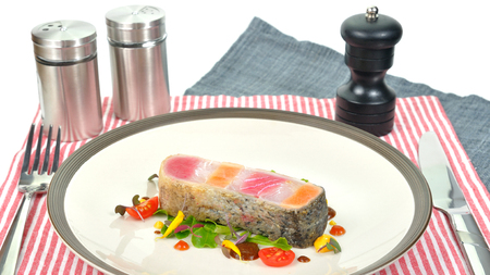 Raw fish steak design lay on white plate. Napkin knife salt bottle pepper bottle pepper grinder.