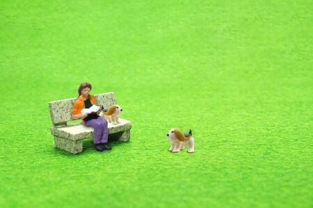 Selective focus miniature sitting on stone bench reading book with beagle dog, business concept.