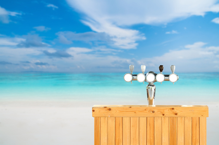 Draft beer dispenser and wooden counter on beautiful beach, Party time.