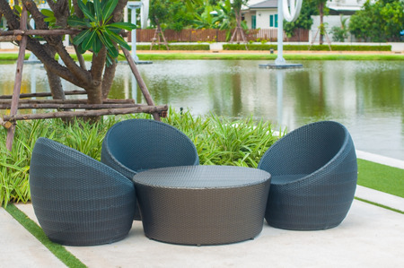 Black outdoor rattan sofa set for rest and relax next to lake in public park. Stock Photo