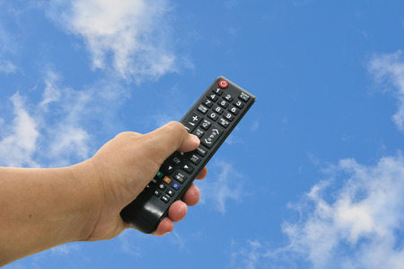 Man had use black remote control point up to blue sky.