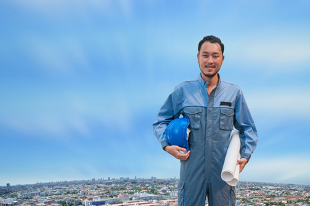 Portrait Asian engineer man hold blue safety helmet with work drawing with building in city.