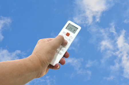 Man had use white air condition remote control point up to blue sky. 25 degree Celsius preventive from Global warming.