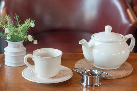 White tea pot and cup with Tea strainer on wooden table, relaxing with hot tea during tea break.