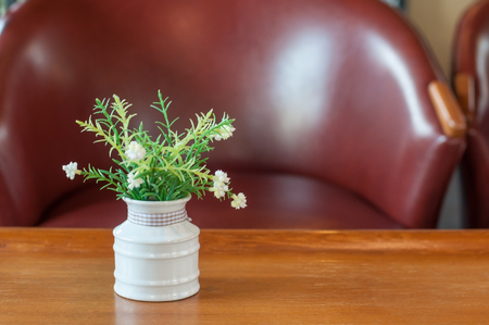 Artificial flower in white pot on wooden table and luxury leather arm chair, home interior concept.
