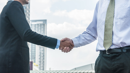 Business people standing and shaking hand after success meeting at  Central business district Stock Photo
