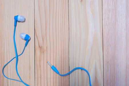 Blue in ear headphone lay on wooden table. Stock Photo