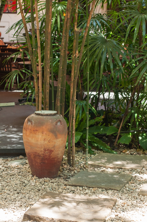 Vintage and retro grunge jar next to bamboo tree in park.