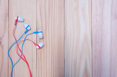 Blue and red in-ear headphone lay on wooden table.