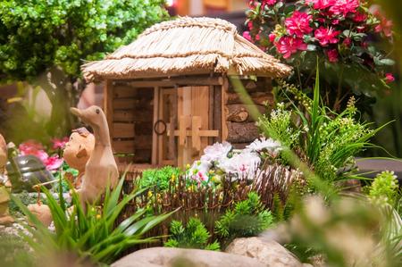 Selective focus miniature artificial flower garden and hut.