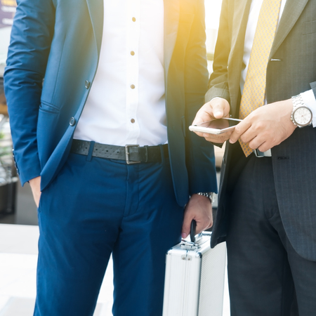Unidentified business people standing and holding briefcase discussion something. Stock Photo