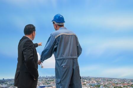 Asian business manager discussing with engineer for planning construction city view with blue sky, Bangkok Thailand.
