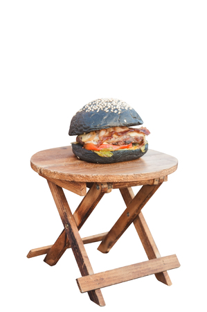 Small circular wooden table with black cheese and bacon burger, clipping path included. Stock Photo