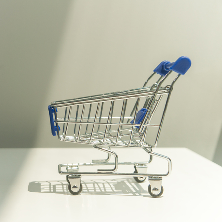 Shopping cart on white table next to gray wall and two tone light.