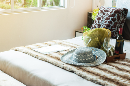 Classic modern bedroom and brown cloth, has a hat flower and leather tray with bottle of wine on bed. Bedroom decoration in modern style. Editorial