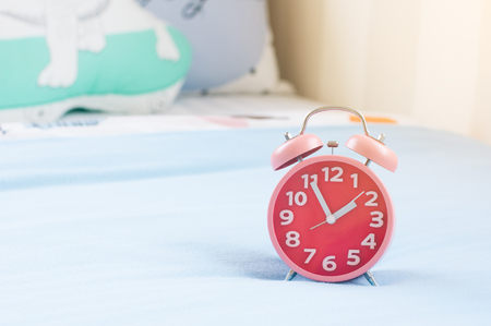 Close up red alarm clock show 5 minutes to 2 o clock on soft bed with blur pillow background.