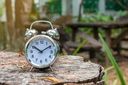 Silver classic alarm clock 10 o' clock lay on wood plank and blur background in park.