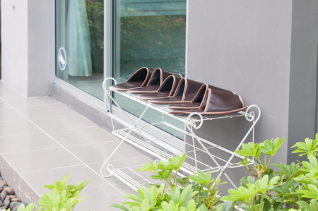 Many slipper arrange on white shelf next to modern sliding door with green tree. Home decoration.