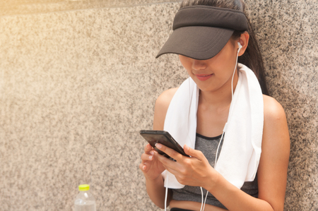 Asian woman wearing gray sport-wear and white towel enjoy with smartphone after exercise in city s high building. Stock Photo