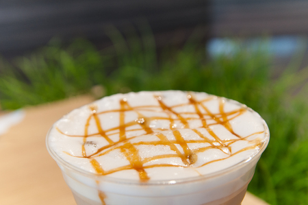 Gold caramel topping on white cream in coffee cup with green grass background.