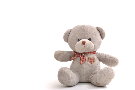 Grey bear doll siting on white background. Stockfoto