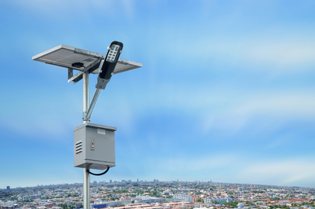 Solar panel lighting pole with cityscape with blue sky and white clouds. Renewable Energy concept.