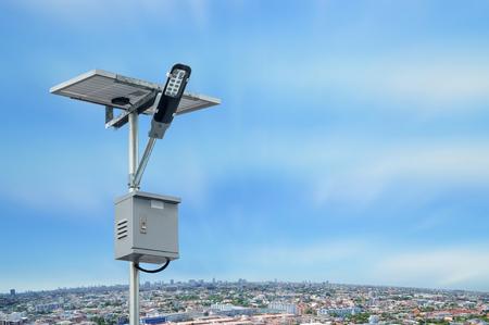 Palo di illuminazione del pannello solare con paesaggio urbano con cielo blu e nuvole bianche. Concetto di energia rinnovabile.