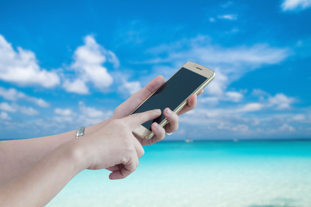 Unidentified woman hand holding and using smartphone for chat social online transaction business and checking email with seascape background. Stock Photo
