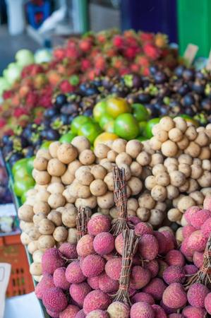 Asian Thai fruit lychee orange and rambutan sales on foot path.