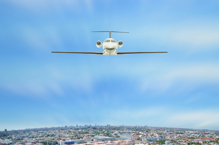 Personal jet airplane flying above city view with blue sky, Thailand. Imagens