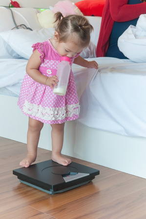 Cute child 1 year and 2 months with baby milk bottle step up on personal Weight Scale in bedroom nexto white bed with her mother. Banque d'images