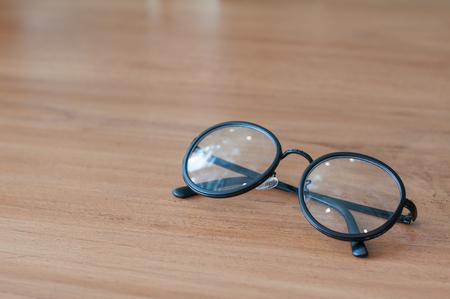 Black classic eye glasses lay on wooden table