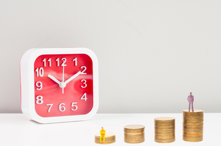 Selective focus miniature woman sitting on the golden coins stack and blur red alarm clock, business conceptual money growth up increases with time.