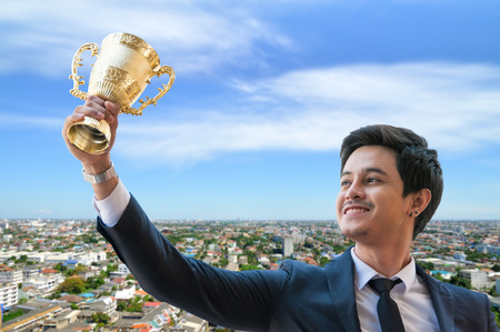 Success business man holding golden trophy cup with right hand, Business executives rejoice in their leadership in business competition.  Congratulations to the gold trophy with blur city town. Stock Photo