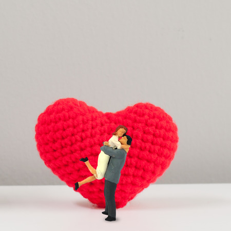 Selective focus miniature male female couple lover jumping hug in front of big red knitting wool heart, valentine conceptual.