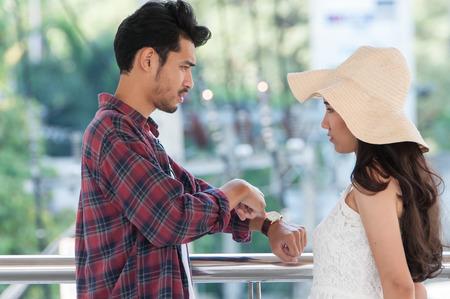 Hombre vestido con camisa de manga larga estar enojado mujer que lleva un vestido blanco con gran sombrero de verano