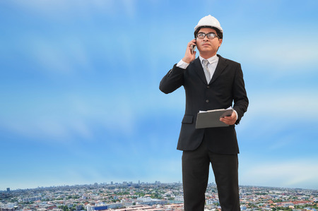 Middle Asian engineer wearing glasses white safety helmet holding construction plan and using smartphone to contact team with blur cityscape bird eye view with blue sky background.