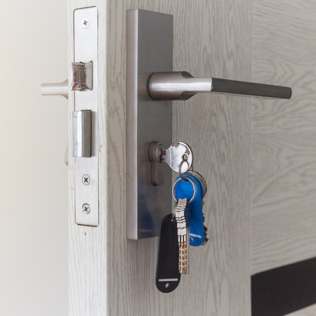 Wooden door with silver handle and house key with key ring with blue black tag is plugged in for open or lock the door. Фото со стока