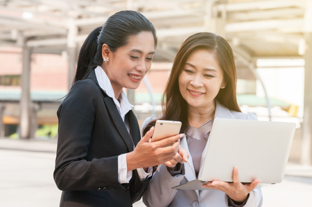 Middle Asian businesswomen coworker happy smile use laptop and smartphone show and updated job description and success plan in middle city town,  people use mobile data update content social media.