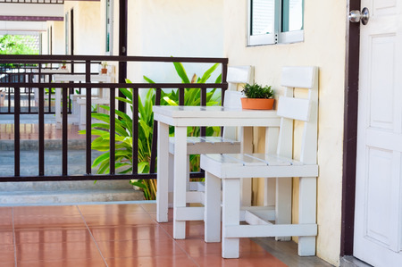 White table and chairs in front of house near wooden fence and next to closed door in morning time.  The atmosphere of bungalow for relaxing in summer vacation.