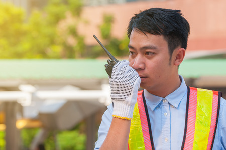 Unhappy young Asian engineer using walkie-talkie personnel radio contact with his team for command and check the project situation in middle city town. Фото со стока