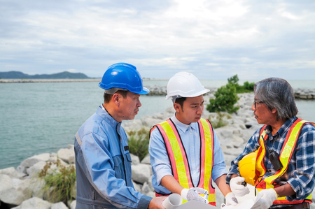 Asian civil engineer team wearing safety helmet and uniform using blueprint to meeting, discussing brain storm for solving their problem situation near big rock for breakwater in Thai Imagens