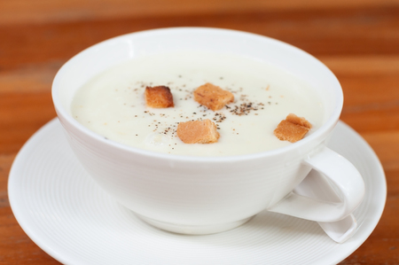 White cup of mushroom soup with crispy bread on wood table, appetizer before main dishes.