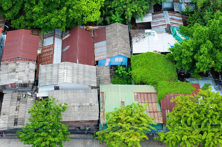 Bird eye view slum houses in Thailand, old houses with zinc roof and big green tree.