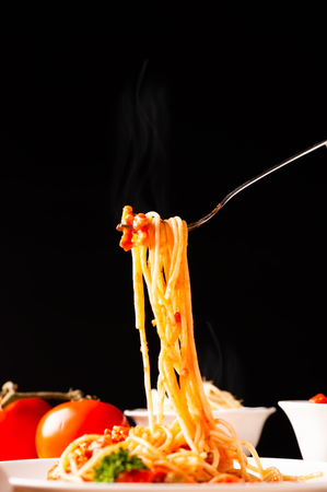 Hot spaghetti with tomato sauce in white plate,  food stylish action with black background, pull spaghetti up with fork.