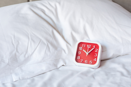 Square red alarm clock on white bed white pillow in bedroom, alarm clock show 10 o clock.  Life time concept.