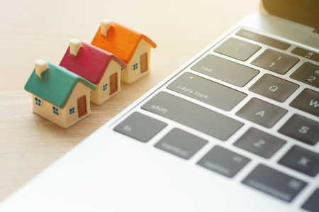 Miniature houses mortgage next to modern laptop with copy space, Real estate online investment and business house loaning marketing on internet.