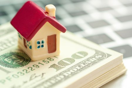 Real estate business concept, dollar banknote with miniature house mortgage, modern online marketing in real estate business. Stock Photo