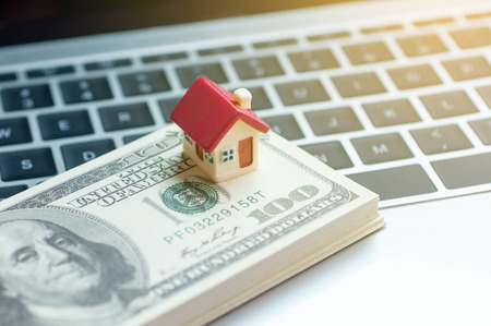 Real estate business concept, dollar banknote with miniature house mortgage, modern online marketing in real estate business. Stockfoto