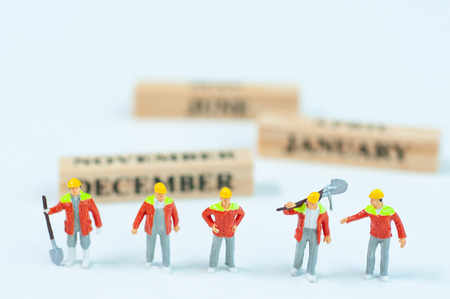 Selective focus miniature civil engineer and worker working set up with calendar wooden blocks 31 December end of year, celebration concept.